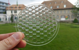 Image of hexagonal lens array as printed by Luximprint with old heritage in the back. The lens array is optically clear and smooth straight from the 3D printing platform. No post-processing such as polishing or grinding is applied.