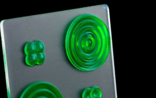 Image of 3D printed green circular fresnel lenses with frosted finish on substrate sheet.