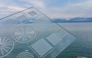 Image of handheld lens plate by Luximprint showing various micro lens features. In the back ground Lake Geneva