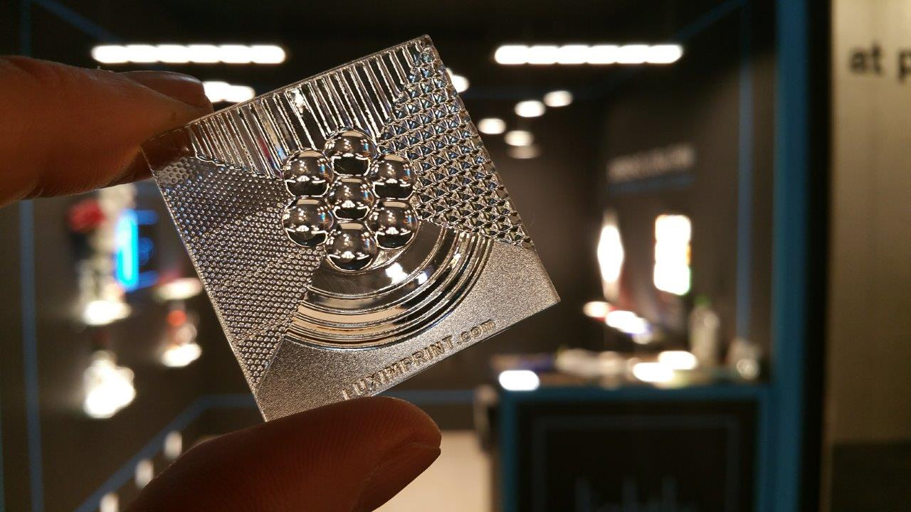 Image of 3D Printed Optics hand sample in front of Lightly Tech booth