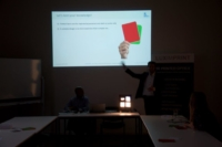 Image of workshop play green and red cards expressing their opinion about the proposed statements