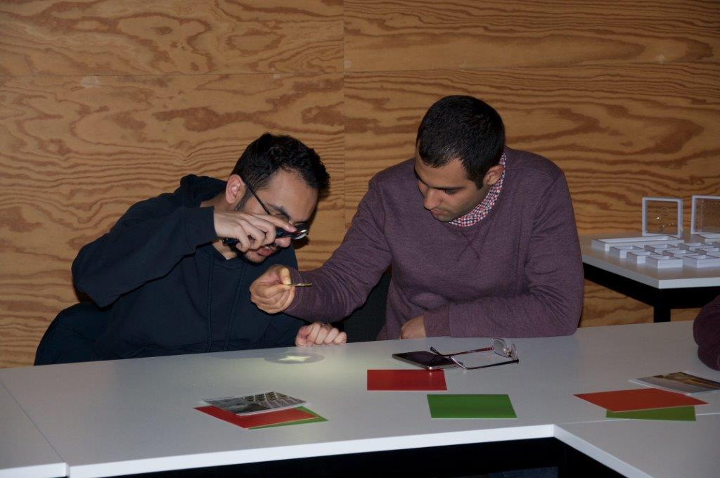 Image of two Photonics master students testing the performance of faceted lens technology.