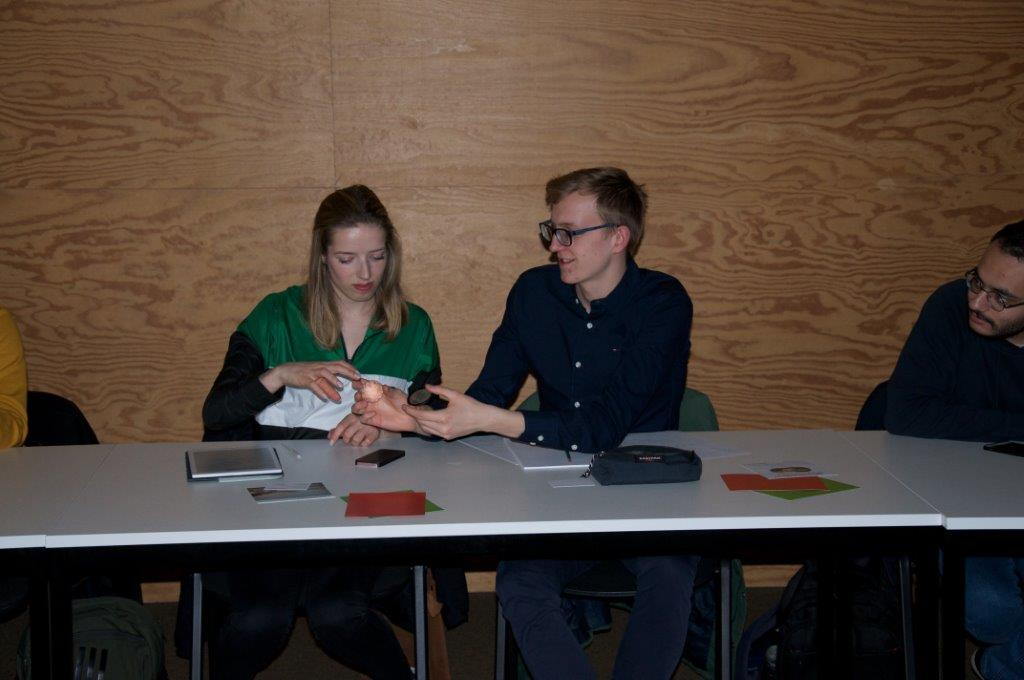 Image of two Photonics students discussing the possibilities with 3D printed optics.